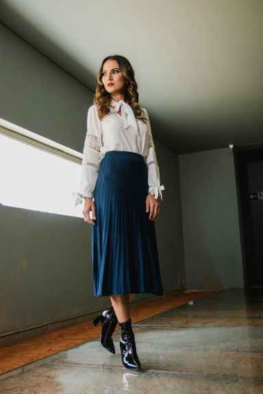 woman wearing white long sleeved shirt and blue skirt
